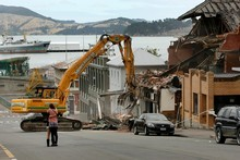 Diggers demolish a damaged building in Lyttleton as residents console one another. Photo / Brett Phibbs