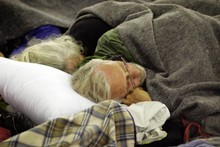 An elderly couple take refuge and sleep in an evacuation centre, set up at Hagley Park. Photo / Sarah Ivey