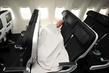 Rob Fyfe,  CEO of Air New Zealand, sleeps on a Skycouch, which is still to be approved by the CAA. Photo / Herald on Sunday
