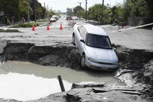 An abandoned car rests in a massive hole in Mackenzie Ave in Christchurch. Photo / Greg Bowker