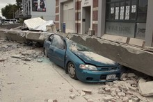 A car is crushed by a beam in central Christchurch. Photo / AP