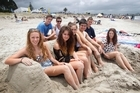 From left, Bryony Miller, Alex Smail, Andy Graham, Johanna Jacobson, Kathy Marshall, Jackson Garden-Bachop, Tom Rowe and Lucy Riddle relax at Whangamata. Photo / NZ Herald