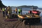 Rescue workers attend to a man pulled from the surf at Hot Water Beach Monday. Photo / Supplied