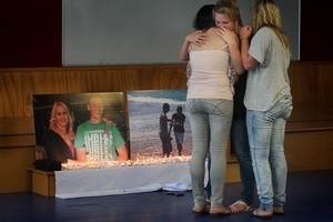 Friends grieve in front of a memorial dedicated to college students  Dylan Perkinson and Vance Williams who died in a horror car smash  near Waihi last January. Picture / Alan Gibson