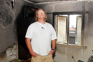Owner Seamus McKenna surveys the damage after a fire at his Ranch Road house in Mount Maunganui. Photo / Mark McKeown