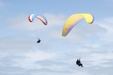 The writer and his training buddy paraglide over Kariotahi beach. Photo / Supplied