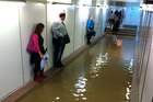 Commuters stand clear of flooding in a Sydney underground railway station. Photo / Supplied