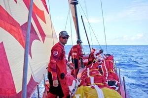 Mike Pammenter dragging sails forward in light winds onboard Camper. Photo / VOR