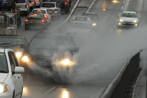 A car drives through water lying on the roadway on the Cahill Expressway in Sydney as heavy rain falls on March 8, 2012. Photo / AFP