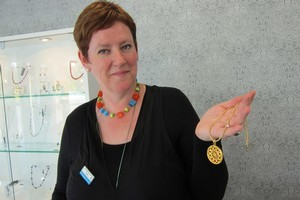 Beadz Unlimited shop assistant Paula Cornborough with one of its rose window pendants. Photo / Amanda Cropp