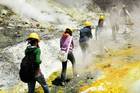 Tourists disappear into the sulphurous mist on a trek around White Island. Photo / Alan Gibson