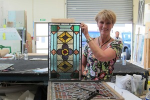 Glass Room co-owner Dorothy Ratcliff with one of 44 windows repaired from a building at Rangi Ruru Girls' School.Photo / Amanda Cropp