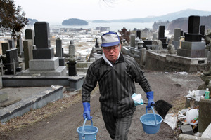 Takayuki Sato carries buckets of water to clean the family grave in Minamisanriku, nearly a year after the March 11 tsunami hit his home town. Photo / AP
