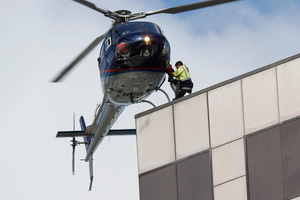A helicopter picks up a police officer from the roof of the PWC Building in central Christchurch, 24 February 2011. Photo / Mark Mitchell