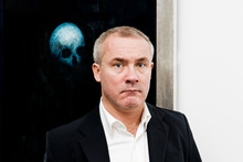 Artist Damien Hirst posing in front of his painting 'Floating Skull'. Photo / Supplied