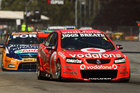 Jamie Whincup, pictured in battle at the Clipsal 500, will stay with Team Vodafone for another three years. Photo / Getty Images