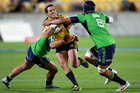 Tim Bateman of the Hurricanes is tackled during the game against the Highlanders. Photo / Getty Images