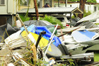 Housing debris is seen in the front yard of a home in Townsville, Australia. Photo / Getty Images