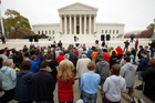Christians kneel on the footpath in front of the Supreme Court as part of 'Encircle the Court in Prayer,' on the eve of arguments on  healthcare legislation. Photo / AP
