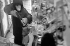 The robber, who police say may be a young person, points a gun at Zai Xing Lin. Photo / Michael Cunningham