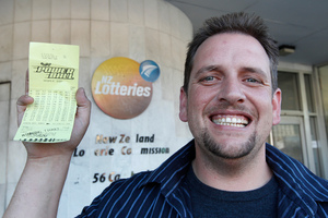Te Kauwhata supermarket check-out operator Trevor with his winning $26,000,000 Lotto ticket at the NZ Lotteries Commission in Wellington. Photo / Mark Mitchell