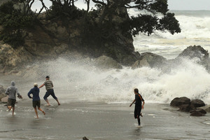 Wild surf whipped the shoreline and spectators were caught out as waves and debris crashed around them on the walkway between the main beach and Leisure Island at Mt Maunganui. Photo / Alan Gibson