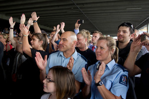Constables Eddie Pene and Melanie Irwin join the 1200 crowd at the Manukau police station yesterday in listening to Jon Toogood and his band Shihad. Photo / Richard Robinson