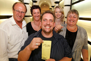 Trevor holding his wining ticket, with family and friends. Photo / Mark Mitchell