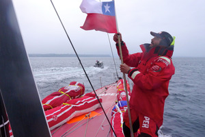 A Chilean flag is hoisted by Roberto Bermudez De Castro presented by the Chilean Navy as Camper approach Porto Montt. Photo / Hamish Hooper.