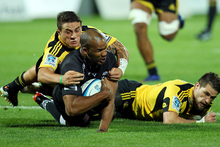 JP Pietersen of the Sharks is tackled by TJ Perenara (L) and Cory Jane of the Hurricanes. Photo / Getty Images