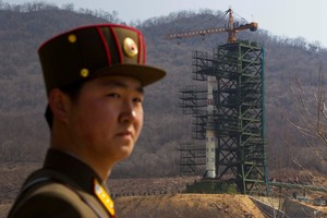 2012 file photo, a North Korean soldier stands in front of the country's Unha-3 rocket, slated for liftoff between April 12-16, at a launching site in Tongchang-ri. Photo / AP