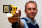 File photo of a police officer holding a loaded Taser.
