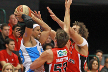 Damian Martin and Matt Knight of the Wildcats defend CJ Bruton of the Breakers. Photo / Getty Images