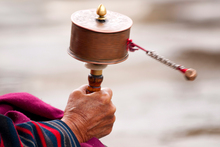 A women spins her prayer wheel in Bhutan, where happiness is valued above almost everything else. Photo / Thinkstock