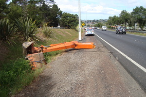 The arm of a digger lies next to the Northwestern Motorway after the accident yesterday. Photo / AMA/NZTA