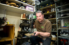 Auckland cobbler Karl Thornley says shoes made of veneer leather over cardboard are difficult to repair. Photo / Michael Craig