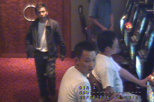 CCTV footage from SkyCity casino's VIP lounge shows Tac Kin Voong (walking) and Ri Tong Zhou (seated wearing glasses). Photo / Supplied