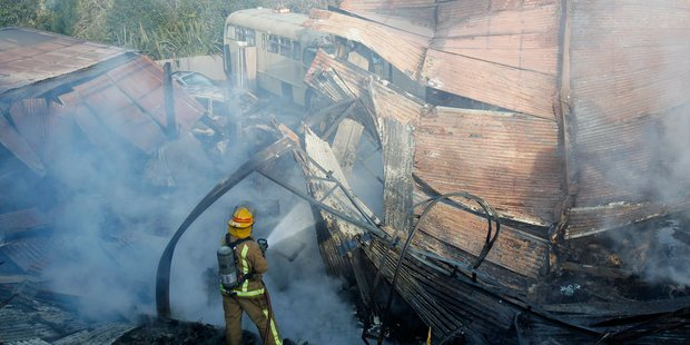 A fireman damps down hotspots at the barn that housed the 1968 Corvette Stingray. Photo / Christine Cornege