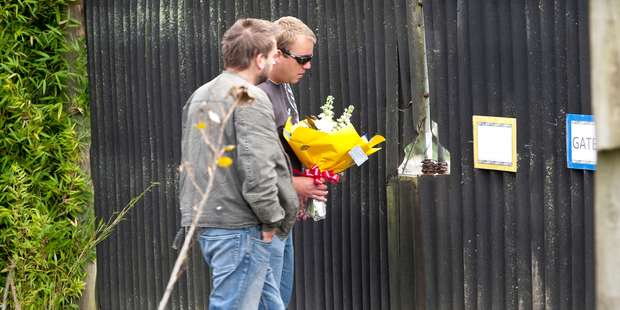 Two men take a floral tribute to Franklin Zoo, which has also received messages of support and donations. Photo / Dean Purcell