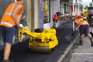 A crew from Downer EDI Works lays hot-mix to give the footpaths in Katikati's Main St. Photo / APN