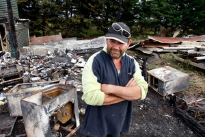 Brett Fowlie surrounded by the ashes of his dream home after a deliberately lit fire destroyed building materials. Photo / Northern Advocate