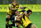 Tusi Pisi (L) and Charlie Ngatai of the Hurricanes tackle Jacques Botes of the Sharks. Photo / Getty Images.