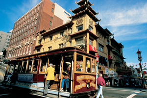 A cable car passes the landmark 1908 Sing Chong Building in Chinatown, San Francisco. Photo / SFCVB