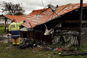 Fire investigators pictured at work on the remains of the house that was destroyed by fire in Rotorua. Photo / APN