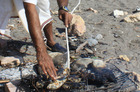 A fisherman cooks lunch on the beach in the Omani port town of Quriyat. Photo / Jim Eagles