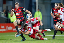 Luke Romano of the Crusaders jumps out of a Reds tackle. Photo / Getty Images
