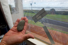 One of the rocks that smashed a window and glass panel. Photo / Brett Phibbs