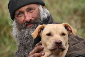 Rowan Hargreaves with one of his dogs, Chicken, the only surviving puppy of a dog massacre. Photo / Natalie Slade