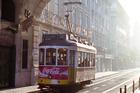 A tram makes its way along a Lisbon street at sunset. Photo / Mark Fryer
