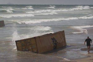 Beach goers are dwarfed by shipping containers on Waihi Beach as some of the debris from the stricken container ship Rena washes ashore. Photo / Greg Bowker